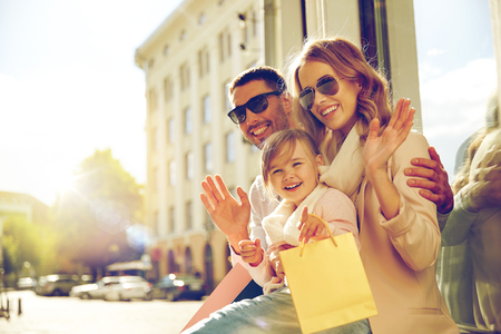 sale, consumerism and people concept - happy family with little child and shopping bags waving hands at shop window in city Stock Photo