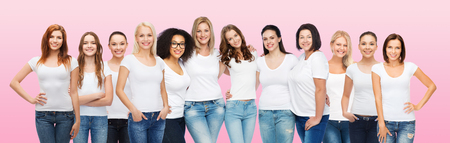 friendship, diversity, body positive and people concept - group of happy women of different age size and ethnicity in white t-shirts hugging over pink background Stock Photo