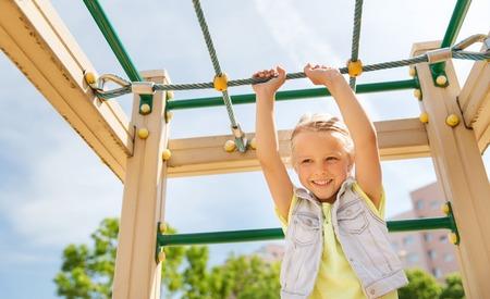 niño escalando: verano, la infancia, el ocio y el concepto de la gente - niña feliz en parque infantil columpio