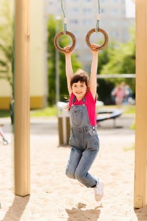 ropa de verano: verano, la infancia, el ocio y el concepto de la gente - niña feliz que cuelga en los anillos gimnásticos en el patio de los niños