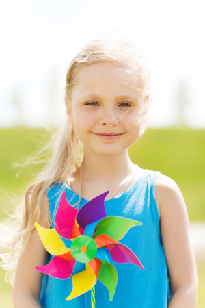 six girls: summer, childhood, leisure and people concept - happy little girl with colorful pinwheel toy outdoors Stock Photo