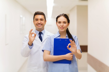 healthcare, profession, people and medicine concept - smiling doctor and nurse with clipboard showing ok hand sign at hospital