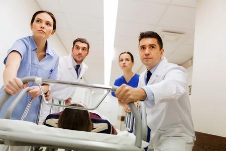 paciente en camilla: profesión, la gente, la atención sanitaria, la reanimación y el concepto de la medicina - grupo de médicos o médicos que llevan paciente mujer inconsciente en la camilla de hospital de emergencia Foto de archivo