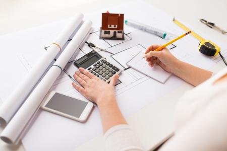 negocio, arquitectura, construcción, construcción y concepto de la gente - cerca de la mano del arquitecto con el modelo en la calculadora