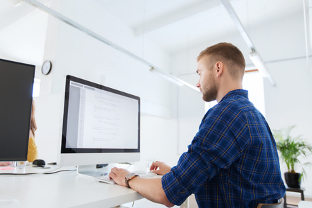 business, tecnologia, educazione e persone Concetto - giovane creativo o il programmatore con il computer di lavoro in ufficio