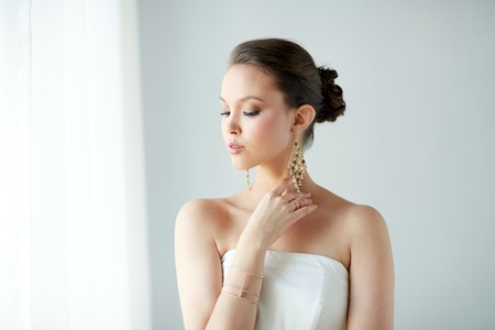 bride bangle: beauty, jewelry, wedding accessories, people and luxury concept - beautiful asian woman in white dress or bride with golden earrings and bracelet Stock Photo