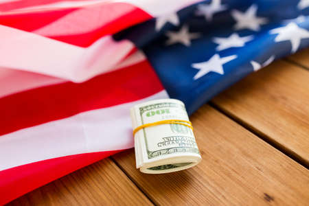 nationalism: budget, finance and nationalism concept - close up of american flag and dollar cash money packet