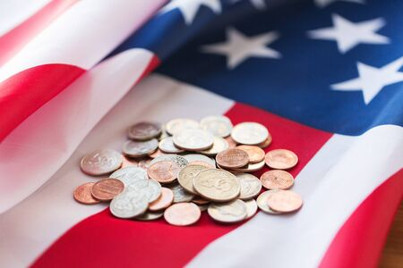 nationalism: budget, finance, money, crisis and nationalism concept - close up of american flag and cent coins