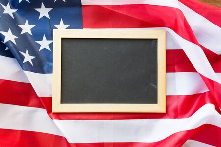 nationalism: education, election, patriotism and nationalism concept - close up of blank school blackboard or chalkboard on american flag Stock Photo
