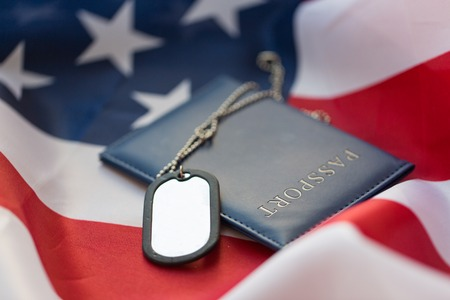 conscription: military forces, patriotism, recruitment and national service concept - close up of american flag, passport and military badge