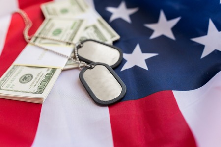 conscription: military forces, recruitment, financing and national service concept - close up of american flag, dollar money and military badges Stock Photo
