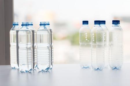 concept de recyclage, de saine alimentation et de stockage des aliments - gros plan de bouteilles en plastique avec de l'eau potable pure sur la table