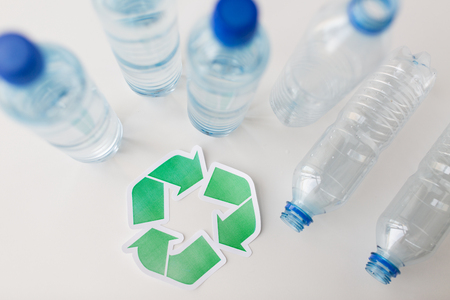 green environment: recycling, reuse, garbage disposal, environment and ecology concept - close up of empty plastic water bottles with green recycle symbol on table
