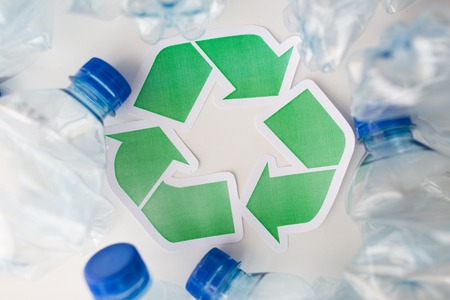 garbage disposal: waste recycling, reuse, garbage disposal, environment and ecology concept - close up of used plastic water bottles with green recycle symbol on table