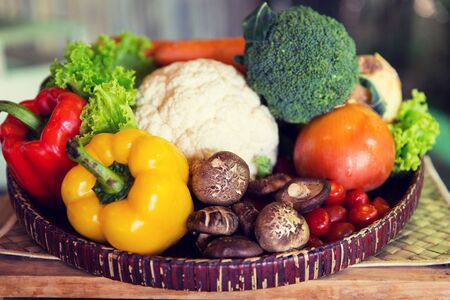 food basket: cooking, kitchen, vegetarian and food concept - basket of of fresh ripe juicy vegetables and mushrooms at kitchen or home