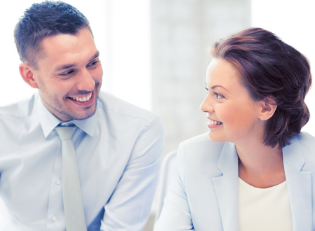 business partners: smiling business team discussing something in office