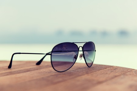 fashon: travel, tourism, summer vacation and fashon accessories concept - shades or sunglasses on table at beach