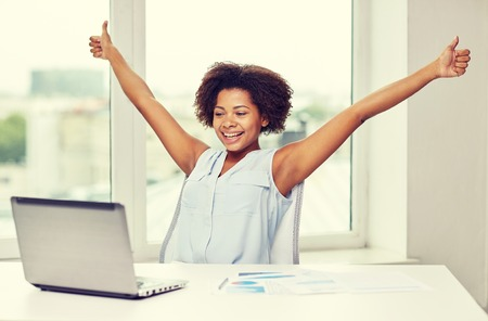 education, business, success, gesture and technology concept - happy african american businesswoman or student with laptop computer and papers showing thumbs up and celebrating triumph at office Фото со стока