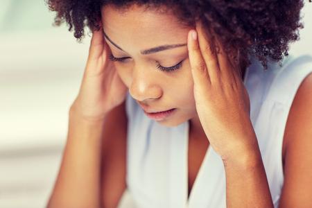 las personas, las emociones, el estrés y el concepto de salud - infeliz mujer joven afroamericana tocando la cabeza y sufriendo de dolor de cabeza