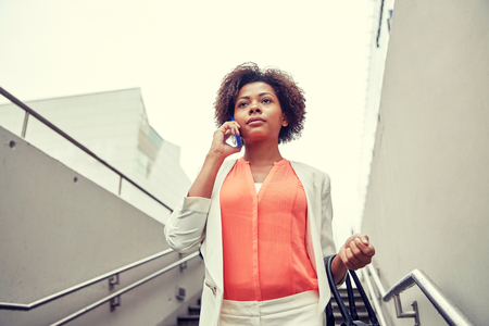 down the stairs: negocio, la comunicación, la tecnología y el concepto de la gente - joven africano americano de negocios que invita al teléfono inteligente bajar escaleras en paso subterráneo de la ciudad Foto de archivo