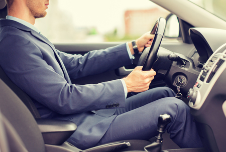 private parts: transport, business trip, destination and people concept - close up of young man in suit driving car