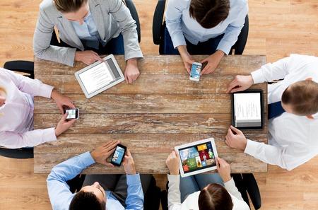 affaires, les gens, la technologie, les médias et le concept de travail d'équipe - close up de l'équipe créative avec les smartphones et les ordinateurs tablette pc assis à une table dans le bureau