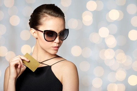 chic: shopping, finances, fashion, people and luxury concept - beautiful young woman in elegant black sunglasses with credit card over holidays lights background