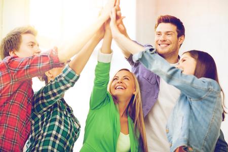 Onderwijs en vriendschap concept - gelukkige studenten geven hoog vijf op school