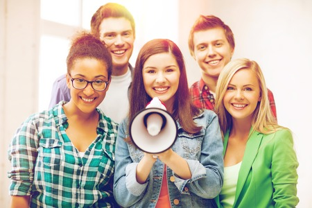education concept - group of students with megaphone at school