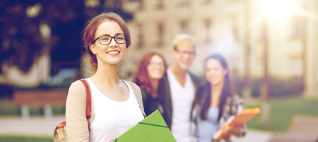 onderwijs, campus, vriendschap en mensenconcept - groep gelukkige tienerstudenten met schoolomslagen Stockfoto