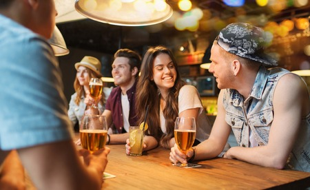 people, leisure, friendship and communication concept - group of happy smiling friends drinking beer and cocktails talking at bar or pub photo