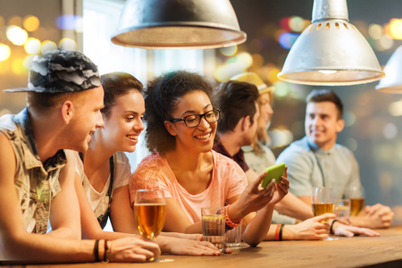 people, leisure, friendship, technology and communication concept - group of happy smiling friends with smartphone and drinks at bar or pub photo