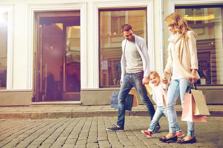 verkoop, consumentisme en mensen concept - gelukkig gezin met een klein kind en boodschappentassen in de stad