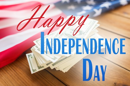 memorial day, patriotism and holiday concept - happy independence day words over american flag and dollar cash money background Stock Photo