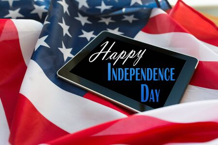 nationalism: technology, memorial day, patriotism and nationalism concept - happy independence day words on tablet pc computer screen on american flag