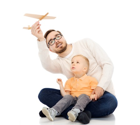 family, childhood, fatherhood, leisure and people concept - happy father and little son playing with toy airplane Reklamní fotografie - 62566318