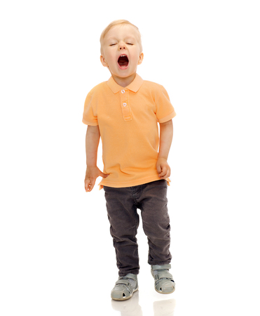 childhood, emotion, expression, fashion and people concept - happy little boy in casual clothes shouting, crying or sneezing Stock Photo