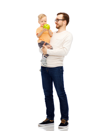 kiddy: family, childhood, fatherhood, healthy eating and people concept - happy father and and little son with green apple