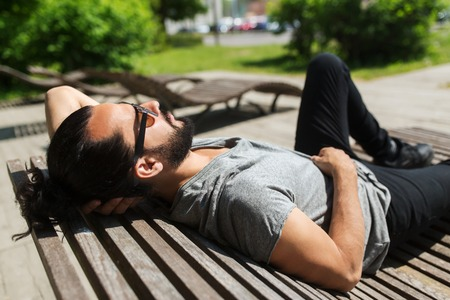 people, leisure and lifestyle - happy man lying on bench or sun bed on street