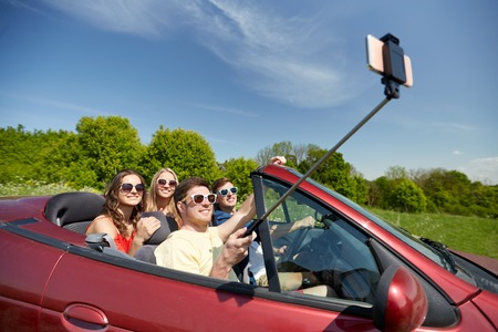leisure, road trip, travel and people concept - happy friends driving in cabriolet taking picture by smartphone selfie stick at country Stock Photo