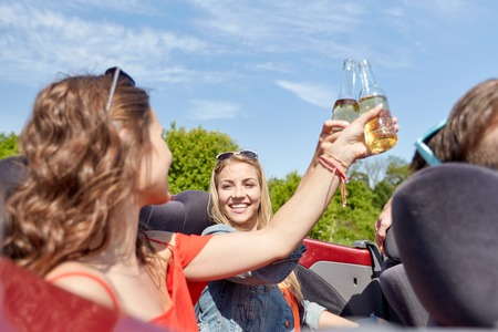 drinking driving: leisure, road trip, travel, summer holidays and people concept - happy friends driving in cabriolet car along country road and drinking beer