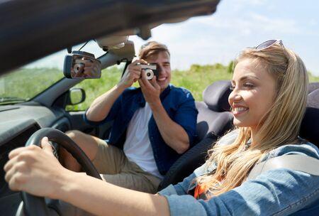 jeune fille adolescente: loisirs, voyage sur la route, Voyage et les gens concept - couple heureux de conduire en voiture cabriolet et prendre des photos par caméra