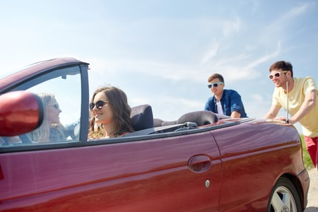 empujando: ocio, viaje por carretera, los viajes y el concepto de la gente - amigos felices empujando el coche roto cabriolet lo largo de la carretera nacional