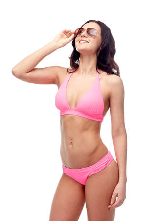 people, fashion, swimwear, summer and beach concept - happy young woman in sunglasses and pink swimsuit looking up