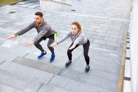 working out: fitness, sport, people, exercising and lifestyle concept - couple doing squats on city street stairs