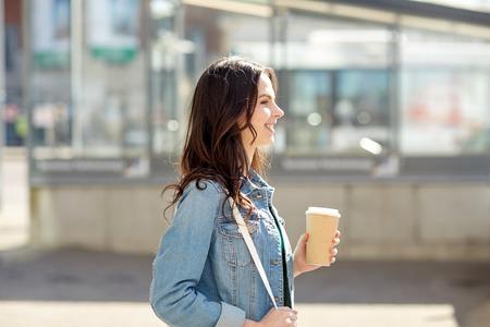 Getränke und Menschen Konzept - glückliche junge Frau oder Teenager-Mädchen Kaffee aus Pappbecher auf Stadtstraße trinken