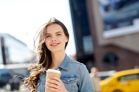 woman young: drinks and people concept - happy young woman or teenage girl drinking coffee from paper cup on city street