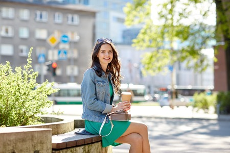 drinks and people concept - happy young woman or teenage girl with handbag drinking coffee from paper cup sitting on on city street bench