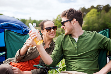 clinking: camping, travel, tourism, hike and people concept - happy friends clinking glass bottles and drinking cider or beer at campsite Stock Photo