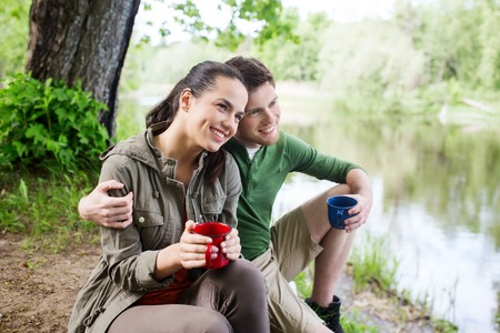 travel, tourism, hike, camping and people concept - happy couple with cups drinking tea in nature on river bank Stock Photo